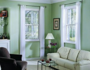 Corner of a furnished living room with green walls that have a double-hung white-frame window on each wall